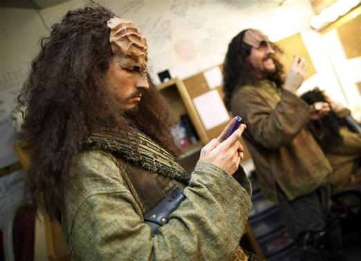 Performer Jon Beal (L) checks his email as Josh Zagoren puts on his make-up for a performance in 'A Klingon Christmas Carol' in Chicago, December 20, 2012. The play is an adaptation of Charles Dickens' classic tale 'A Christmas Carol' and is translated into the Klingon language and adapted to Klingon culture. Klingons are a fictional alien culture that originated from the Star Trek television series. REUTERS/Jim Young
