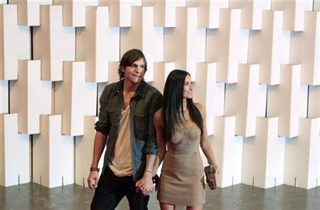 Actor Ashton Kutcher and his wife actress Demi Moore (R) arrive for Colcci's Winter 2011 collection during Sao Paulo Fashion Week January 30, 2011. REUTERS/Nacho Doce