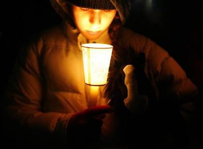 A boy takes part in a candlelight vigil in Newtown, Connecticut, December 21, 2012. REUTERS/Eric Thayer