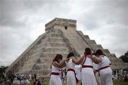 People perform a ritual in front of the pyramid of Kukulkan at the archaeological site of Chichen Itza in Yucatan State, December 21, 2012. Thousands of mystics, hippies and tourists celebrated in the sunshine of southeastern Mexico on Friday as the Earth survived a day billed by doomsday theorists as the end of the world and a new era began for the Maya people. New Age dreamers, alternative lifestyle gurus and curious onlookers from around the world descended on the ruins of Maya cities to mark the close of the 13th bak'tun - a period of around 400 years - and many hoped it would lead to a better era for humanity. REUTERS/Victor Ruiz Garcia