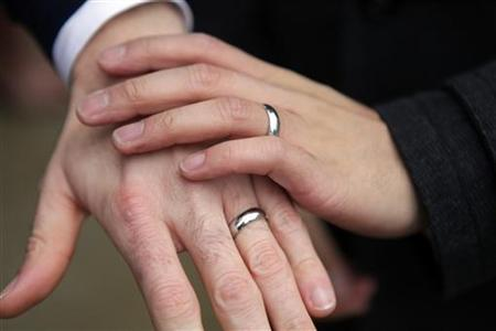 Bernie Liang (L), and Ryan Hamachek, show their rings after getting married outside Seattle City Hall in Seattle, Washington December 9, 2012. REUTERS/Cliff Despeaux/Files