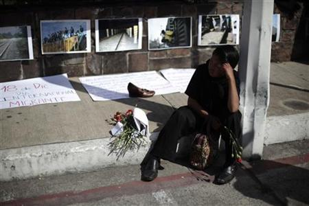 A boy sits next to a shoe and pictures of migrants on the southern border of Mexico, which have been put up outside the Mexican embassy to symbolize the crossing of Central American migrants between Mexico and U.S., in commemoration of the 22nd anniversary of International Migrants Day in Guatemala City, December 18, 2012. REUTERS/Jorge Dan Lopez