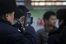 A policeman films his co-workers trying to persuade protesters from gathering near the Beijing Olympic Tower December 22, 2012. REUTERS/Petar Kujundzic