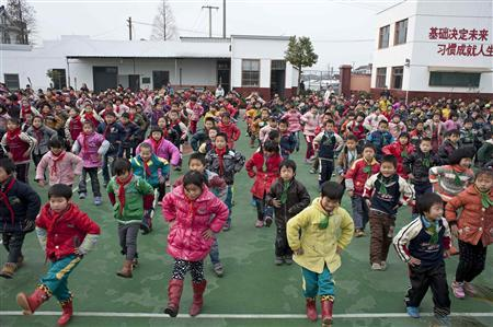 Students do exercises on playground at a primary school for children of migrant workers in Shanghai, December 18, 2012. REUTERS/Darcy Holdorf