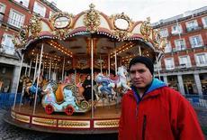 """Hace algunos años, en la boyante España del """"boom"""" del ladrillo, los nuevos edificios se poblaban de papanoeles que trepaban por sus balcones a dejar regalos, y la mayoría de los españoles no se imaginaban deseando trabajar en Navidades. En la imagen, José Luis posa en un carrusel en una feria navideña en Madrid, el 20 de diciembre de 2012. REUTERS/Andrea Comas"""