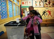 Los egipcios votaban el sábado el borrador de Constitución elaborado por grupos islamistas, en la segunda ronda de un referéndum que se espera apruebe un texto al que sus detractores acusan de crear más inestabilidad en Egipto. En la imagen, una niña deposita el voto de su padre en la segunda ronda del referéndum sobre la Constitución egipcia en el distrito de El Arbeen, Suez, 120 kilómetros de El Cairo, el 22 de diciembre de 2012. REUTERS/Mohamed Abd El Ghany