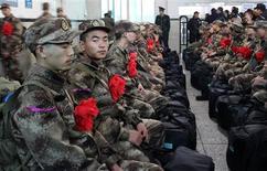 China ha prohibido a militares de alto rango la celebración de banquetes en los que haya alcohol o alojarse en hoteles de lujo cuando se encuentren en viajes de trabajo en la última medida del jefe del Partido Comunista, Xi Jinping, para luchar contra la corrupción, informaron medios locales el sábado. En la imagen, nuevos reclutas del Ejército de Liberación del Pueblo con flores rojas que simbolizan el honor, esperando para subir a un tren en la estación de Mayang Miao, en la provincia de Hunan, el 13 de diciembre de 2012. REUTERS/China Daily