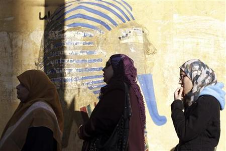 Women queue near a graffiti of pharaoh King Tutankhamun outside a polling centre to vote during the final stage of a referendum on Egypt's new constitution, in El Dokki district of greater Giza, south of Cairo, December 22, 2012. REUTERS/Amr Abdallah Dalsh
