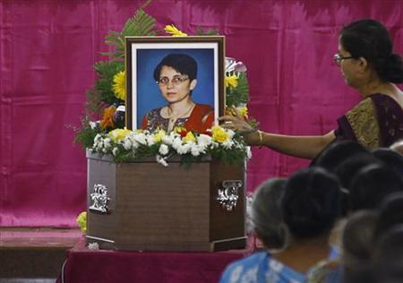 A woman puts flowers on Jacintha Saldanha's coffin during her funeral inside a church in Shirva, about 52 km (32 miles) north of Mangalore December 17, 2012. REUTERS/Stringer
