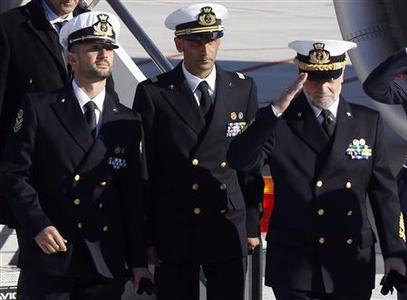Italian marines Salvatore Girone (L) and Massimiliano Latorre (C) arrive with Italian Navy Chief of Staff Admiral Luigi Pinelli Mantelli at Ciampino airport in Rome, December 22, 2012. Two Italian marines charged with killing two fishermen off the coast of India are likely to spend Christmas in Italy, after an Indian court on Thursday accepted the sailors' request to be allowed to join their families for the holiday season. REUTERS/Alessandro Bianchi