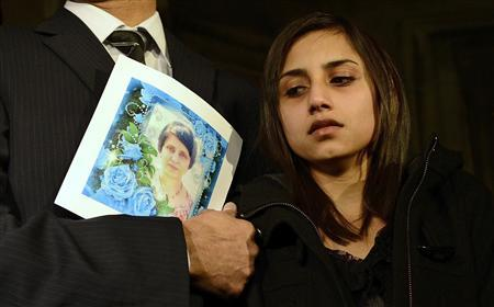Lisha Barboza, standing with her father Ben, looks towards a picture of her late mother, nurse Jacintha Saldanha, as they leave the Houses of Parliament in London in a December 10, 2012 file photo. REUTERS/Dylan Martinez/files