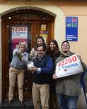 Jose Luis Serrano (C) and family, owners of a lottery shop that sold the number of the second prize of 'El Gordo', celebrate outside their shop in Aranda de Duero, December 22, 2012. The total prize money of 2.5 billion euros ($3.32 billion) is split into thousands of cash prizes amongst hundreds of winning numbers. REUTERS/Ricardo Ordonez