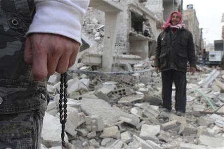 A resident holds prayer beads near another man near buildings, damaged by what activists said were missiles fired by a Syrian Air Force fighter jet of forces loyal to Syrian President Bashar al-Assad, at Douma near Damascus December 17, 2012. Picture taken December 17, 2012. REUTERS/Karm Seif/Shaam News Network/Handout (SYRIA - Tags: POLITICS CIVIL UNREST RELIGION) FOR EDITORIAL USE ONLY. NOT FOR SALE FOR MARKETING OR ADVERTISING CAMPAIGNS. THIS IMAGE HAS BEEN SUPPLIED BY A THIRD PARTY. IT IS DISTRIBUTED, EXACTLY AS RECEIVED BY REUTERS, AS A SERVICE TO CLIENTS