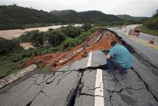 Um homem inspeciona uma rodovia parcialmente destruída por chuvas próximo à cidade de Sapucaia, 104 quilômetros ao nordeste do Rio de Janeiro. 10/01/2012 REUTERS/Ana Carolina Fernandes