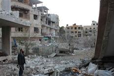 Un coche bomba mató el sábado a cinco personas e hirió a decenas en el distrito de Qabun, en el este de Damasco, según el Observatorio Sirio de Derechos Humanos. En la imagen, un combatiente del Ejército Libre de Siria juntoa edificios que según activistas fueron dañados por el fuego de un caza leal al presidente sirio, Bashar el Asad, en Zamalka, cerca de Damasco, el 19 de diciembre de 2012. REUTERS/Karm Seif/Shaam News Network/Handout ESTA IMAGEN HA SIDO PROPORCIONADA POR UN TERCERO. REUTERS LA DISTRIBUYE, EXACTAMENTE COMO LA RECIBIÓ, COMO UN SERVICIO A SUS CLIENTES.