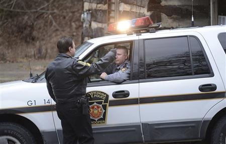 A Blair County Sheriffs deputy talks with an arriving Pennsylvania State Patrol trooper along Route 22 near the entrance to Canoe Creek State Park, in Blair County, Pennsylvania, December 21, 2012. Four people died on a Pennsylvania highway on Friday when a gunman shot dead three people and later was killed in a shootout with police, authorities said. Three state troopers were injured in the incident in Frankstown Township, about 100 miles east of Pittsburgh. REUTERS/Altoona Mirror/J.D. Cavrich