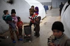 Syrian refugee children gather around a fire to get warm, at Bib Salam refugee camp in Syria near the Turkish border December 22, 2012. International envoy Lakhdar Brahimi will visit Syria in the next few days and is expected to meet President Bashar al-Assad, government officials and some opposition factions, a source in the Arab League said. REUTERS/Ahmed Jadallah