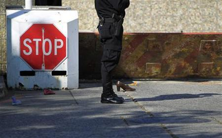 A police officer stands next to shoes placed outside the United States Embassy to symbolize the crossing of Central American migrants between Mexico and U.S., in commemoration of the 22nd anniversary of International Migrants Day in Guatemala City December 18, 2012. REUTERS/Jorge Dan Lopez
