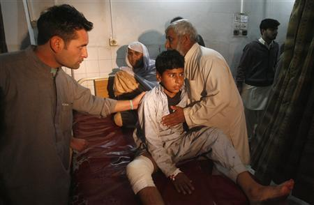 A boy, injured in a bomb blast waits for treatment at a hospital in Peshawar December 22, 2012.Taliban Islamic militants bombed a political rally in Pakistan's northern city of Peshawar on Saturday, killing nine people including a provincial minister, officials said, the latest in a string of high-profile attacks. REUTERS/Khuram Parvez
