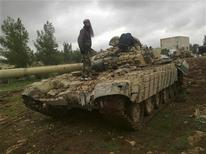 Free Syrian Army fighters inspect a tank after the fighters said they fought and defeated government troops in Al-Latameneh, near Hama December 22, 2012. REUTERS/Redwan Al-Homsi/Shaam News Network/Handout