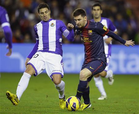 Barcelona's Lionel Messi (R) fights for the ball with Real Valladolid's Oscar Gonzalez during their Spanish First Division soccer match at Zorrilla Stadium in Valladolid December 22, 2012. REUTERS/Ricardo Ordonez