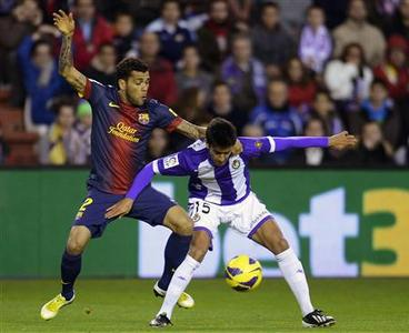 Barcelona's Daniel Alves (L) challenges Real Valladolid's Alberto Bueno during their Spanish First Division soccer match at Zorrilla Stadium in Valladolid December 22, 2012. REUTERS/Ricardo Ordonez