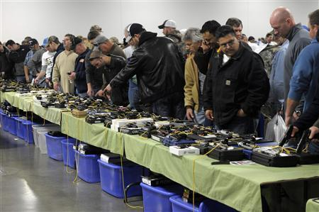 People look over a table of handguns for sale at a gun show in Kansas City, Missouri December 22, 2012. REUTERS-Dave Kaup