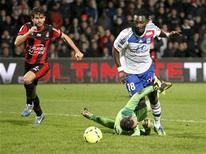 L'attaquant lyonnais Bafétimbi Gomis à la lutte avec le gardien niçois David Ospina, qui a été exclu lors du match. L'Olympique lyonnais a dominé l'OGCN Nice 3-0 au stade de Gerland, samedi, et a pu partir en vacances avec la satisfaction d'avoir rejoint le Paris Saint-Germain au sommet de la Ligue 1 au terme de la 19e et dernière journée de la phase aller. /Photo prise le 22 décembre 2012/REUTERS/Robert Pratta