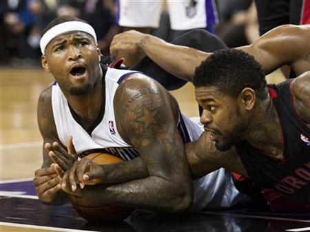 Sacramento Kings' DeMarcus Cousins (L) and Toronto Raptors' Amir Johnson (R) tangle over the ball during the second half of their NBA basketball game in Sacramento, California December 5, 2012. REUTERS/Max Whittaker