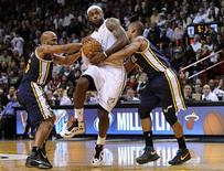 Miami Heat's LeBron James (C) is defended by Utah Jazz Jamaal Tinsley (L) and Randy Foye (R) during the second half of their NBA basketball game in Miami, Florida, December 22, 2012. REUTERS/Rhona Wise