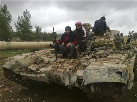 Free Syrian Army fighters pose near a tank after the fighters said they fought and defeated government troops in Al-Latameneh, near Hama December 22, 2012. REUTERS/Redwan Al-Homsi/Shaam News Network/Handout