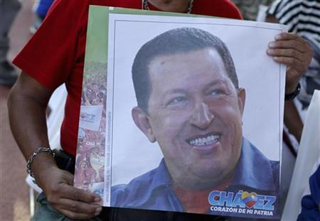 A supporter of Venezuelan President Hugo Chavez holds a picture of him, as he attends a mass to pray for Chavez's health in Caracas December 19, 2012. REUTERS/Carlos Garcia Rawlins (VENEZUELA - Tags: POLITICS HEALTH RELIGION)