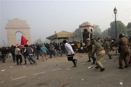 Police wield their batons as they chase away demonstrators in front of the India Gate during a protest in New Delhi December 23, 2012. The Indian government moved on Sunday to stamp out protests that have swelled in New Delhi since the gang-rape of a young woman, banning gatherings of more than five people, but still thousands poured into the heart of the capital to vent their anger. REUTERS/Adnan Abidi