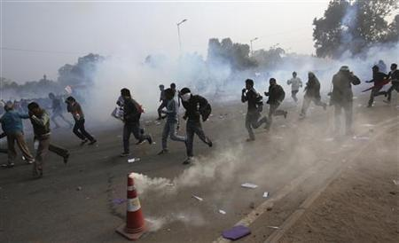 Demonstrators run for cover after police released tear gas to disperse them in front of the India Gate during a protest in New Delhi December 23, 2012. REUTERS/Adnan Abidi