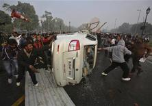 Demonstrators overturn a government vehicle in front of the India Gate during a protest in New Delhi December 23, 2012. The Indian government moved on Sunday to stamp out protests that have swelled in New Delhi since the gang-rape of a young woman, banning gatherings of more than five people, but still thousands poured into the heart of the capital to vent their anger. REUTERS/Adnan Abidi (INDIA - Tags: CRIME LAW CIVIL UNREST TPX IMAGES OF THE DAY)