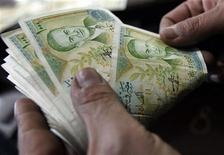A cashier counts Syrian currency notes in Amman December 6, 2011. REUTERS/Ali Jarekji