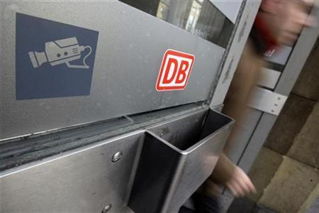A symbol shows an observation camera next to the logo of German railway operator Deutsche Bahn at an entrance door of Frankfurt main station February 6, 2009. REUTERS/Alex Grimm (GERMANY)