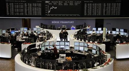 Traders are pictured at their desks in front of the DAX board at the Frankfurt stock exchange December 20, 2012. REUTERS/Remote/Lizza David (GERMANY - Tags: BUSINESS)