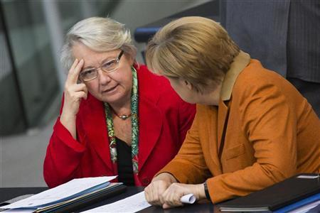German Education Minister Annette Schavan (L) talks with Chancellor Angela Merkel during a session of the Bundestag, the German lower house of parliament, in Berlin October 18, 2012. REUTERS/Thomas Peter