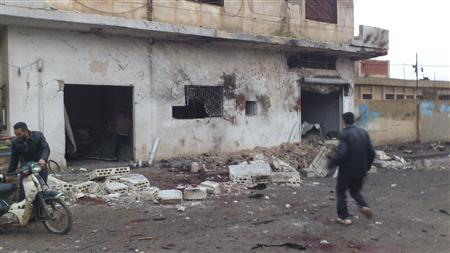 Residents walk near a bakery damaged by what activists said were missiles fired by a Syrian Air Force fighter jet from forces loyal to Syria's President Bashar al-Assad at Halfaya, near Hama December 23, 2012. REUTERS/Samer Al-Hamwi/Shaam News Network/Handout