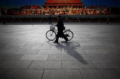 A man walks with his bicycle in front of a screen showing propaganda displays near the Great Hall of the People at Beijing's Tiananmen Square in this November 7, 2012 file photo. Rich Chinese are buying bicycles that cost more than the average citizen makes in three years, motivated by nostalgia for the days when two wheels were the primary means of transport. China is now the world's biggest auto market, but high-end bike sales are expected to grow by 10 percent a year as they become a status symbol for wealthy executives. Picture taken November 7, 2012. REUTERS/Carlos Barria/Files
