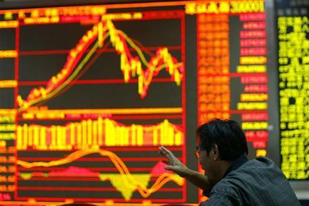 An investor gestures in front of an electronic screen showing stock information at a brokerage house in Wuhan, Hubei province October 9, 2009. REUTERS/Stringer/Files