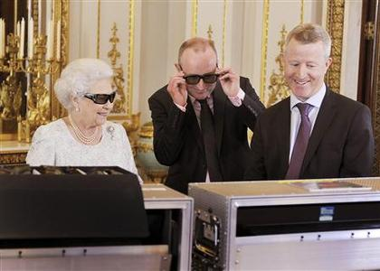Britain's Queen Elizabeth (L) watches a preview of her Christmas message with a pair of 3D glasses, studded with Swarovski crystals in the form of a ''Q'', with producer John McAndrew and director John Bennett (R), at Buckingham Palace in central London in a photo released December 24, 2012. REUTERS/John Stillwell/Pool