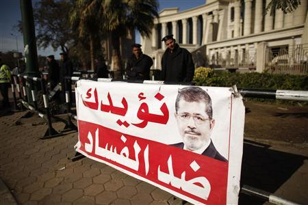 Policemen stand guard near a banner outside the constitutional court put up by supporters of Egyptian President Mohamed Mursi as they stage a sit-in, in Cairo December 23, 2012. Mursi will have little time to savour victory in pushing through a new constitution as it may have cost the Islamist leader broader support for urgent austerity measures needed to fix the creaking economy. The banner reads, ''We support you against corruption!'' REUTERS/Khaled Abdullah