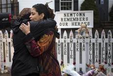 Una superviviente de la masacre en el colegio de Sandy Hook, en la localidad estadounidense de Newtown, en la que murieron 20 niños y seis adultos, contó que la directora y otras dos trabajadoras salvaron su vida y la de otros al advertir de la presencia del hombre armado autor de los disparos. En la imagen del 21 de diciembre, dos mujeres se abrazan tras un minuto de silencio cerca del colegio de Sandy Hook, en Newtown, Connecticut. REUTERS/Adrees Latif