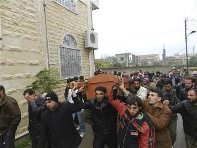 Residents and Free Syrian Army fighters carry the body of Muhammad Abed Al Muati Al-Salah, whom activists say was killed after a Syrian Air Force fighter jet loyal to Syria's President Bashar al-Assad fired missiles, during his funeral in Houla, near Homs December 23, 2012. REUTERS/Mysraa Al-Misrai/Shaam News Network/Handout