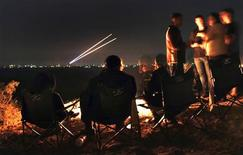 Israeli civilians sitting atop a hill in the city of Sderot watch as two Palestinian rockets fly towards southern Israel, before a ceasefire November 21, 2012. REUTERS/Yannis Behrakis