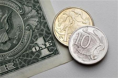 One dollar and 10 cents in Australian currency sit atop a U.S. one dollar note in this photo illustration taken in Sydney July 27, 2011. REUTERS/Tim Wimborne