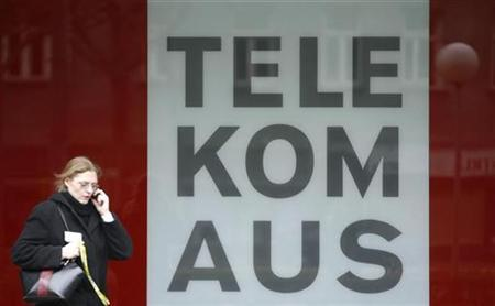 A woman talks on her mobile phone as she walks by Telekom Austria headquarters in Vienna November 10, 2008. REUTERS/Heinz-Peter Bader