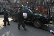 Una afgana que llevaba un uniforme policial mató a tiros el lunes a un contratista civil que trabajaba para las tropas occidentales en la jefatura de policía de Kabul, dijo la OTAN. Unos policías afganos vigilan en el exterior del edificio policial en el que tuvo el ataque el 24 de diciembre en Kabul. REUTERS/Omar Sobhani